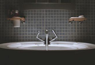 badezimmer mit badewanne und dunklen fliesen