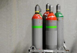 Schutzgasflaschen vier Stück vor grauem Hintergrund