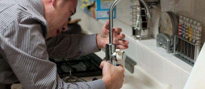 Mann am Reparieren eines Wasserhahns