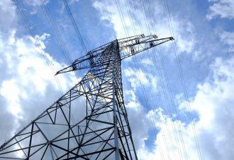Starkstrom-Mast mit Leitungen und blauem Himmel