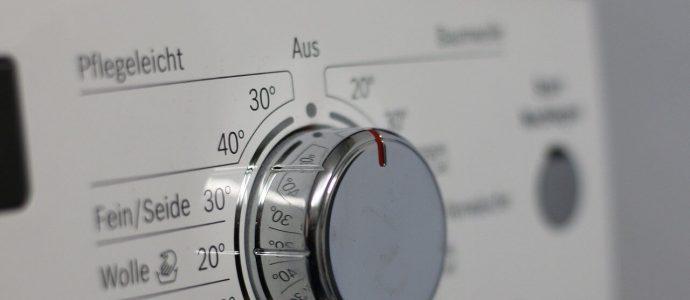 Waschmaschinenknopf iner weißen Waschmaschine und dem Potential für einen Überschrank